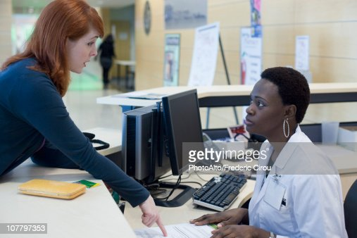 upset patient explaining problem to medical receptionist stock, Human Body