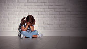 upset sad sad child girl in stress sits and cries at an empty dark wall
