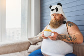 This healthy food is not for me. Sad fat man is holding bowl of cereals and looking at camera with dissatisfaction. He is sitting on couch at home