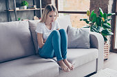 Upset woman has first symptoms of pms. She is sitting on a sofa and  touching her stomach. She is going to cry.