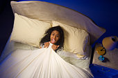 Upset woman lying in bed tugging on sheets