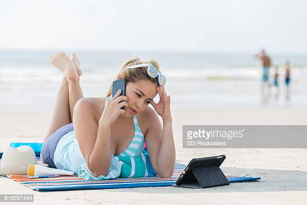 Upset woman with smart phone on a beach vacation