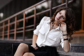 Fashionable glamorous attractive beautiful amazing pretty nice awesome gorgeous girl,student,school girl sitting on stairs near school,university,campus,library.Sad,sorrowful girl think about study.Ge