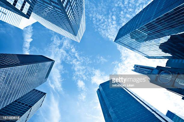 Upshot of tall skyscrapers against blue sky and wispy cloud