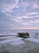 Upside Down Boat On Beach Against Cloudy Sky During Sunset