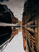 Upside Down Image Of Buildings And Cars Reflection In Puddle