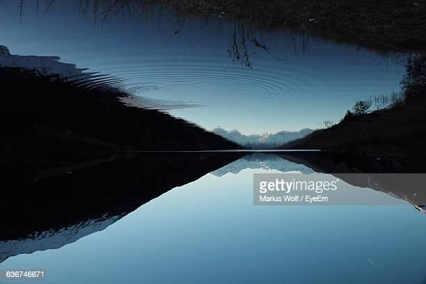 Upside Down Image Of Calm Lake Against Clear Sky At Dusk