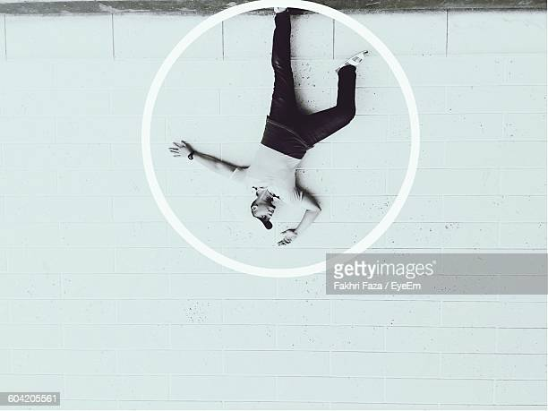 Upside Down Image Of Man Standing Against Wall