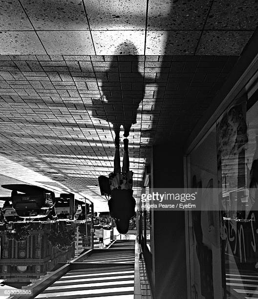 Upside Down Image Of Silhouette Woman Walking On Footpath