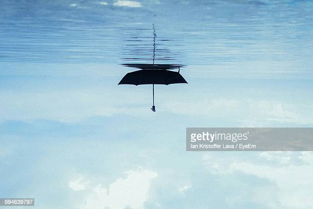 Upside Down Image Of Umbrella Floating On Sea Against Sky