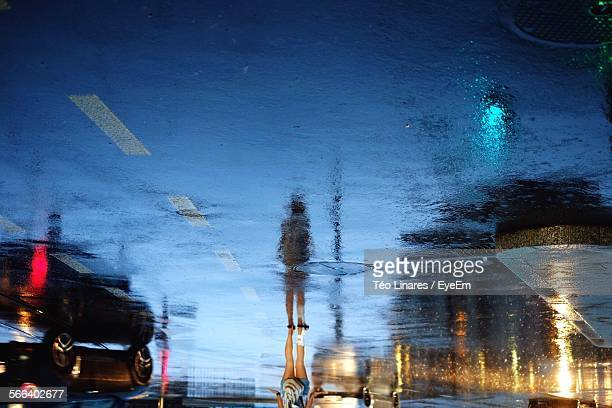 Upside Down Image Of Woman Reflection On Wet Street At Dusk During Monsoon