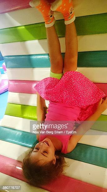 Upside Down Of Cute Smiling Girl Enjoying In Playground