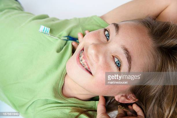 Upside down young girl with braces holding a toothbrush.