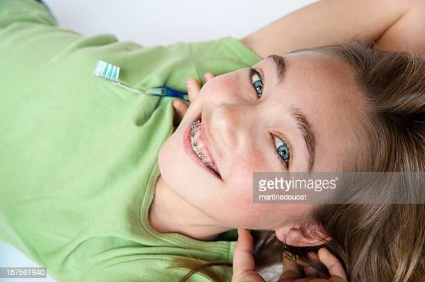 Upside down junges Mädchen mit Zahnspange hält eine Zahnbürste.