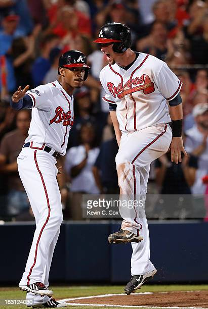 J Upton and Chris Johnson of the Atlanta Braves celebrate after scoring in the seventh inning against the Los Angeles Dodgers during Game Two of the...