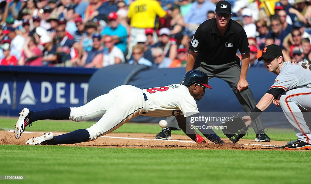 B. J. Upton #2 of the Atlanta Braves dives back to first base against Buster Posey #28 of the San Francisco Giants at Turner Field on June 15, 2013 in Atlanta, Georgia.