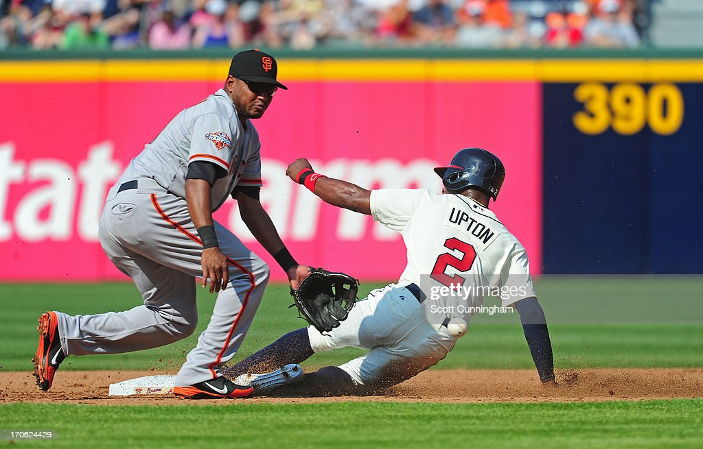 B. J. Upton #2 of the Atlanta Braves steals second base against Tony Abreu #10 of the San Francisco Giants at Turner Field on June 15, 2013 in Atlanta, Georgia.