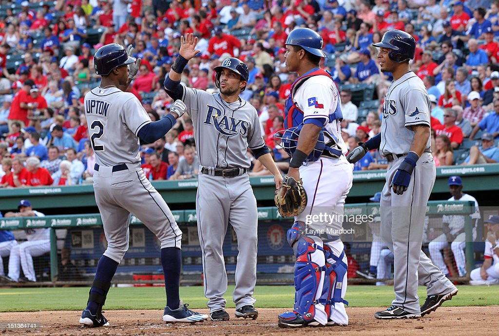 B.J. Upton #2 of the Tampa Bay Rays is congratulated by teammates Sam Fuld (C) and Desmond Jennings (R) after hitting a 3-run homer as catcher Luis Martinez of the Texas Rangers watches on August 29, 2012 at the Rangers Ballpark in Arlington in Arlington, Texas.