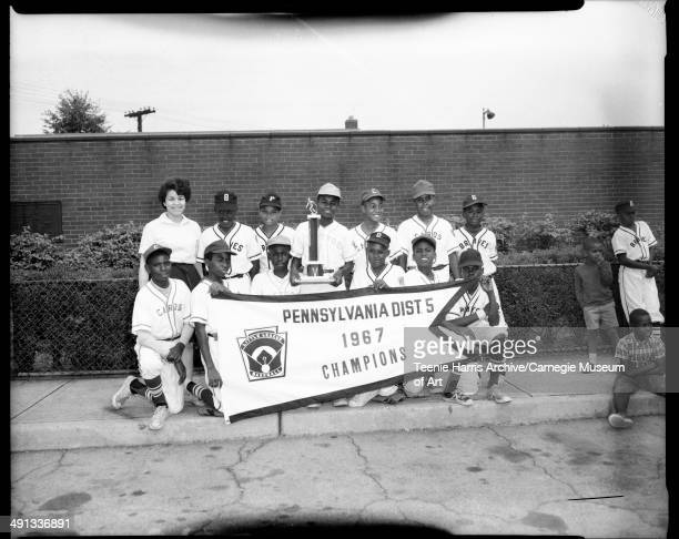Uptown Little League baseball players from Astros Braves and Cardinals 'Cards' teams holding large pennant reading 'Pennsylvania Dist 5 1967...