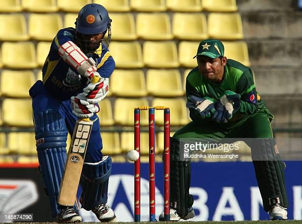 Upul Tharanga of Sri Lanka bats as Pakistan wicketkeeper Sarfraz Ahmed looks on during the first one day international match between Sri Lanka and...