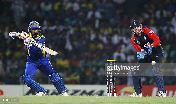 Upul Tharanga of Sri Lanka hits the ball towards the boundary as Matt Prior of England looks on during the 2011 ICC World Cup Quarter Final match...