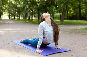 Beautiful sporty young woman working out on street, doing stretching exercises on blue mat in park alley, urdhva mukha shvanasana (upward facing dog pose), sun salutation complex, full length
