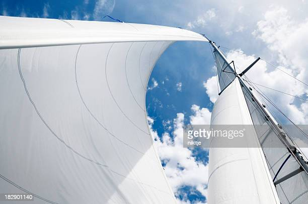 Upward shot of curved white sails against a blue cloudy sky