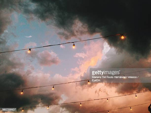 Upward View Of Electric Lights In A Row Against Dramatic Sky