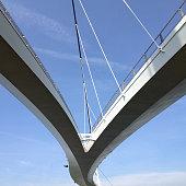 Upward view of suspended bridge against blue sky