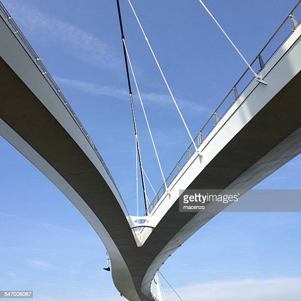Upward view of suspended bridge against blue sky