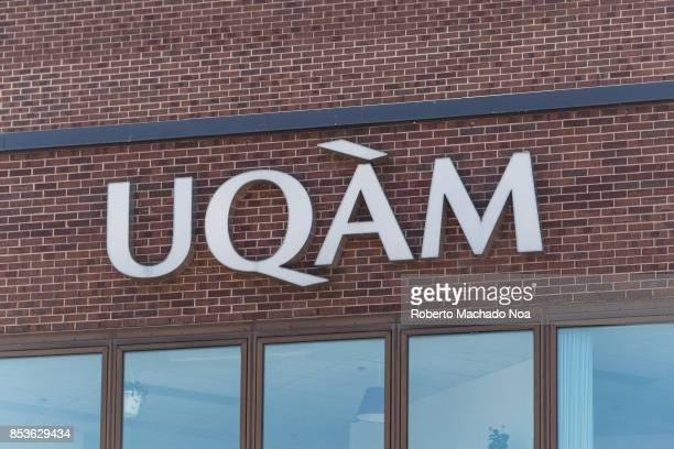 Uqam signage on a brick wall Glass panels below bellow the initials