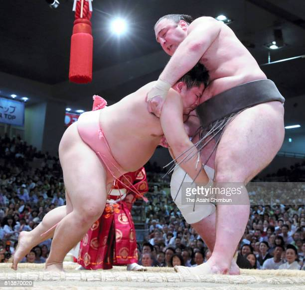 Ura pushes Georgian wreslter Tochinoshin out of the ring to win during day five of the Grand Sumo Nagoya Torunament at Aichi Prefecture Gymnasium on...
