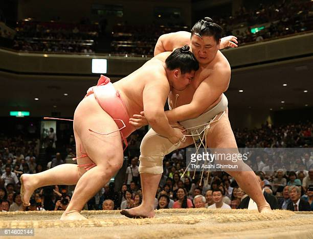 Ura pushes Mongolian Higashiryu out of the ring to win in the Juryo rank during final day of the Grand Sumo Autumn Tournament at Ryogoku Kokugikan on...