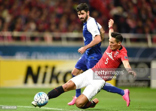 Urawa Red Diamonds' defender Tomoaki Makino clears the ball in front of Al Hilal's forward Omar Khrbin during the second leg of the AFC Champions...