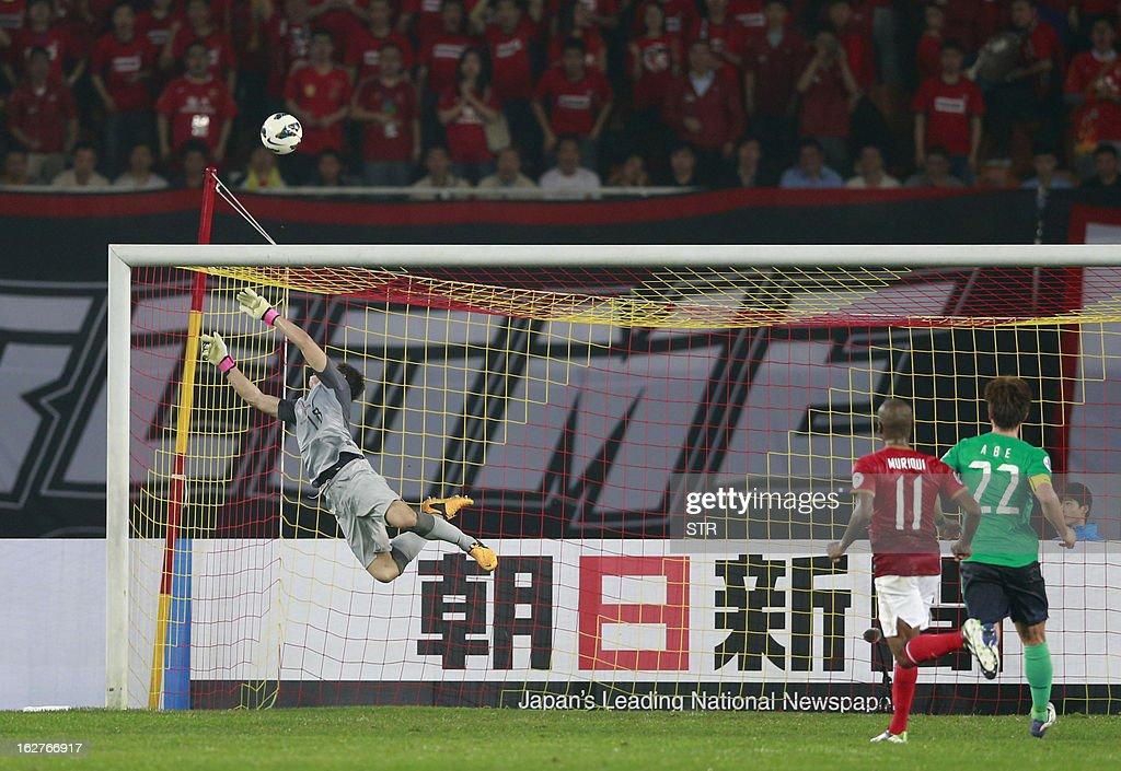 Urawa Red Diamonds' goalkeeper Nobuhiro Kato (L) dives for a shot against Guangzhou Evergrande in the AFC Champions group F match in Guangzhou's Tianhe stadium on February 26, 2013. Guangzhou beat Urawa 3-0.