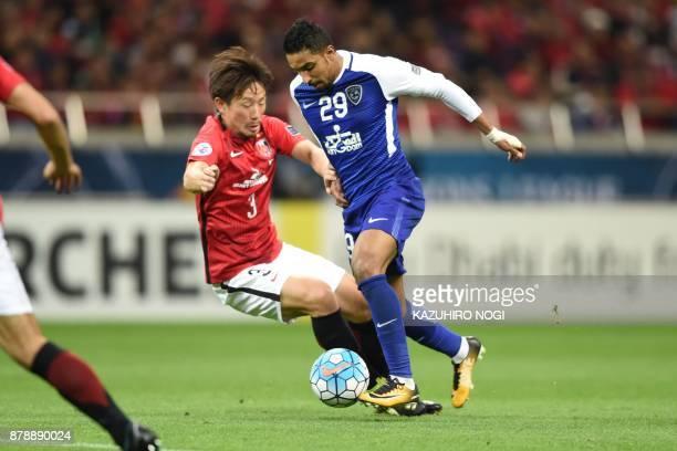 Urawa Red Diamonds' midfielder Tomoya Ugajin fights for the ball with Al Hilal's midfielder Salem alDawsari during the second leg of the AFC...