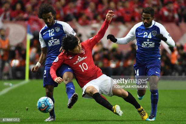 Urawa Red Diamonds' midfielder Yosuke Kashiwagi is tackled by Al Hilal's defender Yasir alShahrani and midfielder Nawaf alAbid during the second leg...