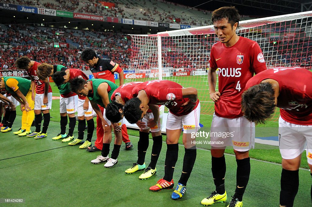 Urawa Red Diamonds players bow for apology to their supporters for the draw after the J.League match between Urawa Red Diamonds and Ventforet Kofu at Saitama Stadium on September 21, 2013 in Saitama, Japan.