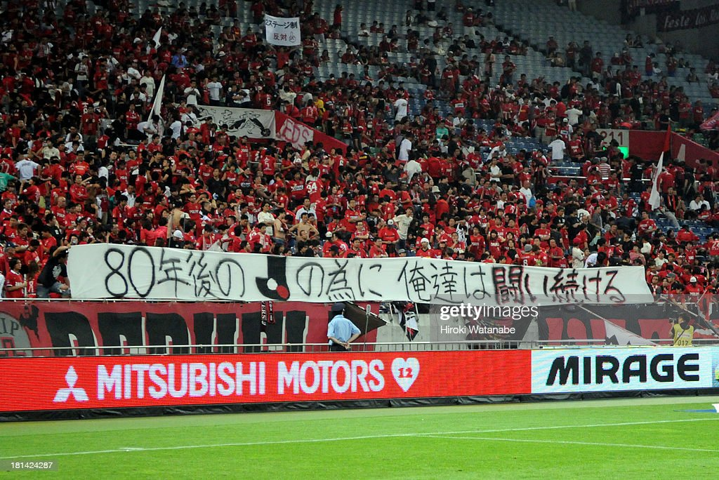 Urawa Red Diamonds supporters hold a banner to protest against the J-League's decision to transfer to two-season system from 2015 prior to the J.League match between Urawa Red Diamonds and Ventforet Kofu at Saitama Stadium on September 21, 2013 in Saitama, Japan.