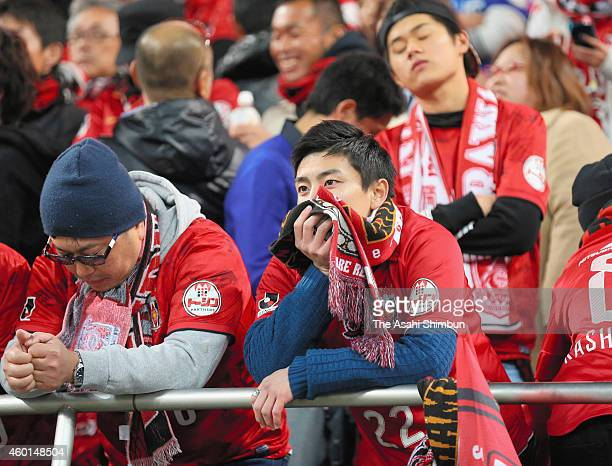 Urawa Red Diamonds supporters show their dejection as their team missed the season champion after their team's 12 defeat in the JLeague match between...