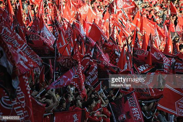 Urawa Red Diamonds supporters wave flags prior to the JLeague match between Urawa Red Diamonds and Gamba Osaka at Saitama Stadium on November 22 2014...
