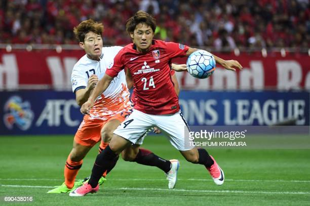 Urawa Reds' midfielder Takahiro Sekine and Jeju United's forward Ahn Hyunbeom compete for the ball during the AFC Champions League round of 16 second...