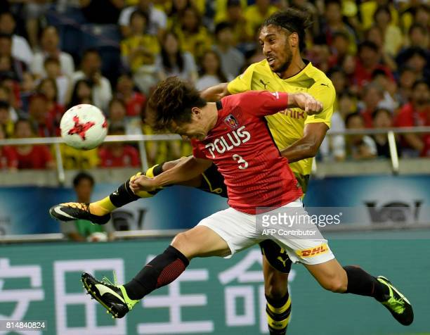 Urawa Reds midfielder Tomoya Ugajin fights for the ball with Dortmund forward PierreEmerick Aubameyang during their friendly football match between...