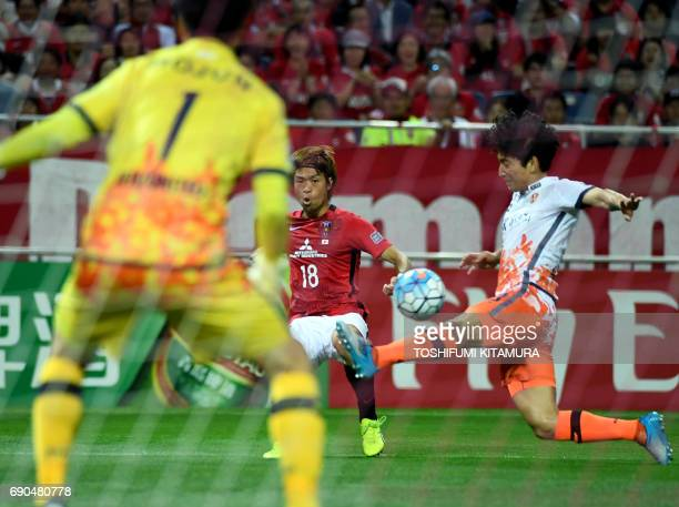 Urawa Reds' midfielder Yoshiaki Komai passes the ball as Jeju United defender Chung Woon attempts a tackle during the AFC Champions League round of...