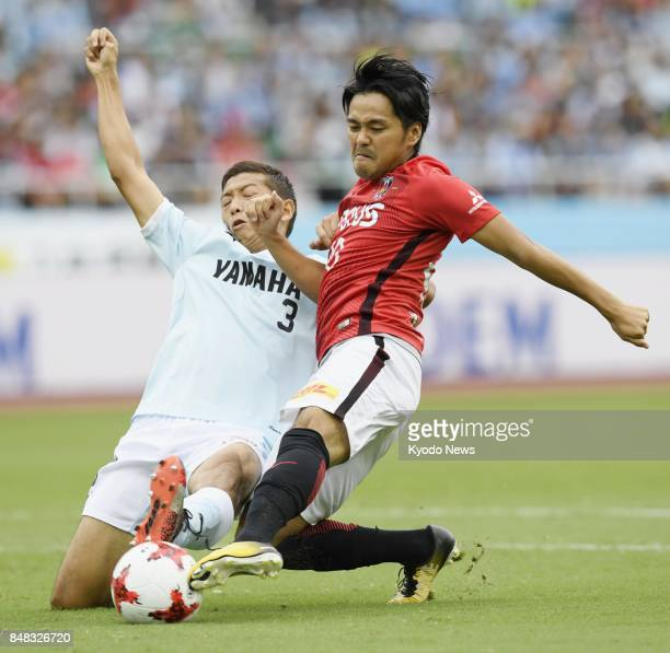 Urawa Reds' Shinzo Koroki and Jubilo Iwata's Kentaro Oi vie for the ball during the first half of a 11 draw in the JLeague first division at ECOPA...