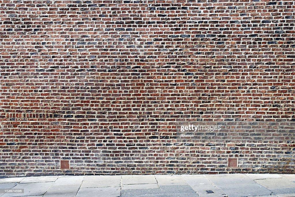 Urban background UK - Red brick wall with sidewalk : Stock Photo