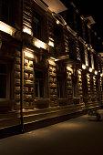 Urban building facade illuminated in warm light on autumn night