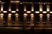 Urban building facade illuminated in warm lights on autumn night