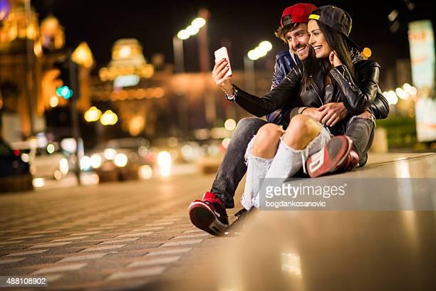 Jeune couple urbain en selfie dans la ville de nuit
