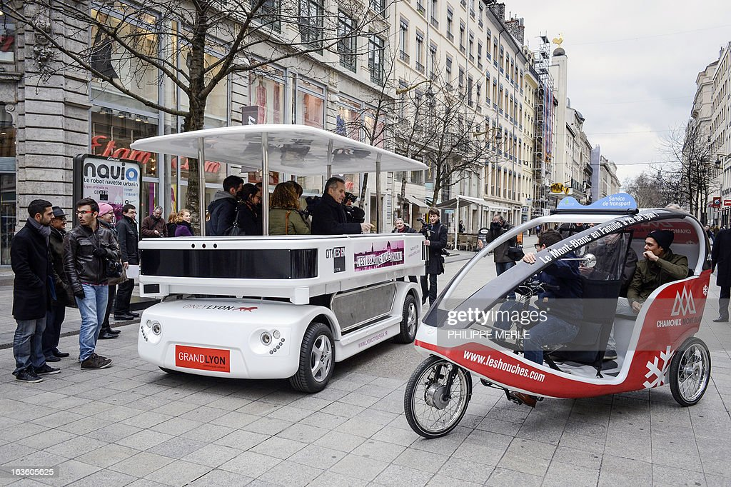 Urban driverless shuttle 'NAVIA' drives past an electric velo-taxi during its launch on march 13, 2013 in the east-central French city of Lyon. NAVIA is a driverless 8 passenger robotized shuttle, design for transportation in city centers. This shuttle is equipped with laser range finders, cameras and a software package that allows it to move autonomously and safely in any environment.